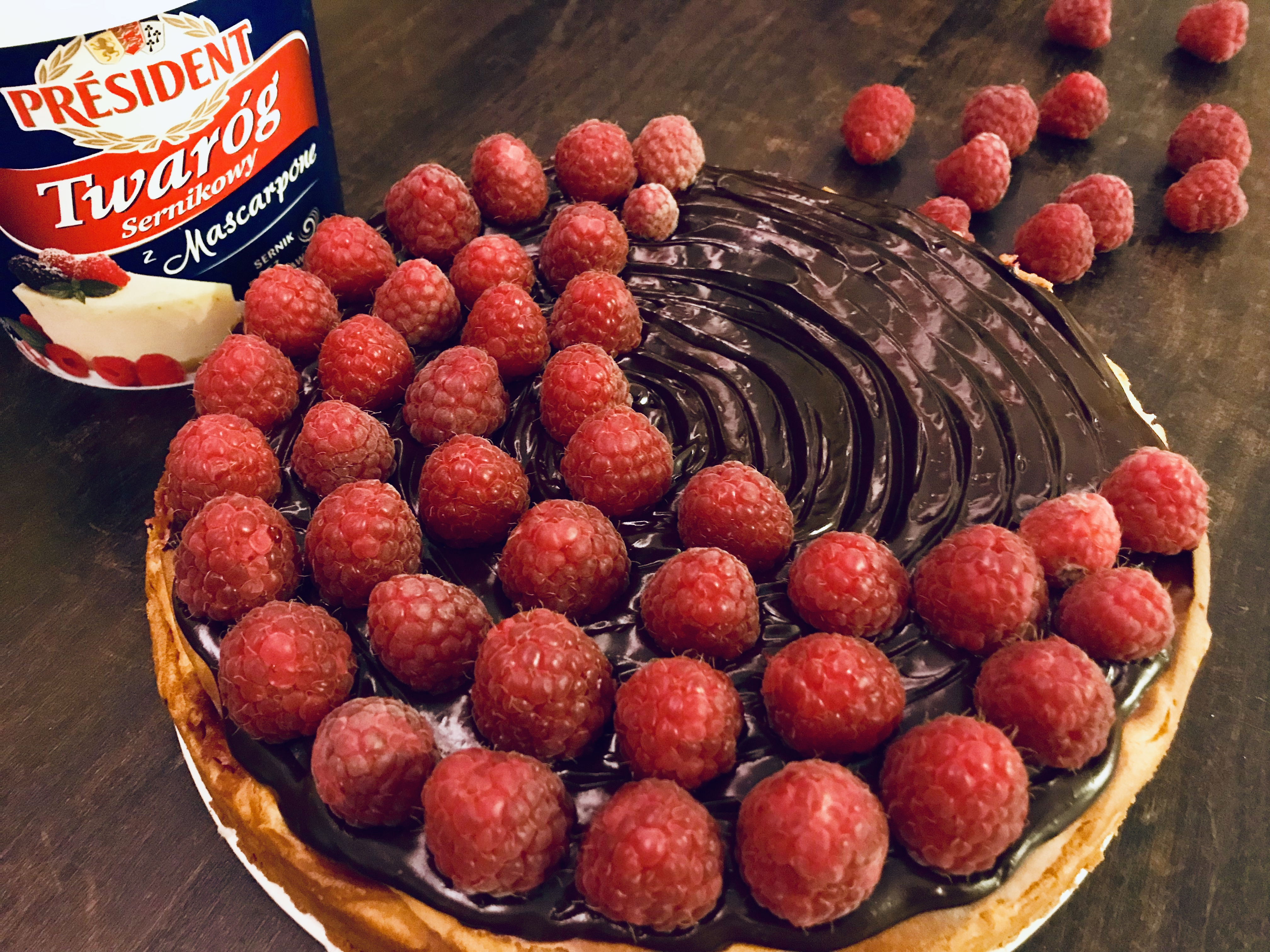 Sernik na parzonym cieście z malinami i kremem czekoladowym.